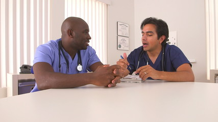 African American and Hispanic doctor talking in hospital