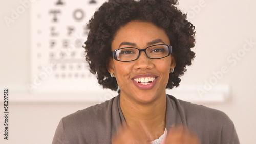 African American woman happy with new glasses at eye doctor