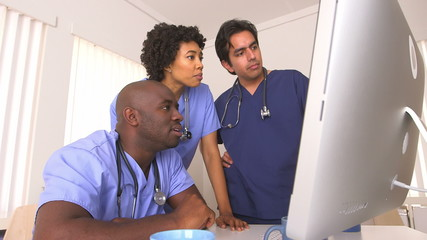 Team of doctors reviewing work on computer