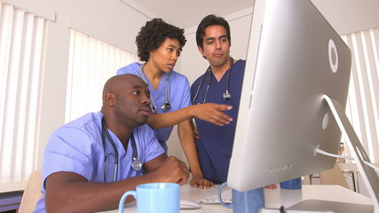 Multi ethnic group of doctors working together at computer
