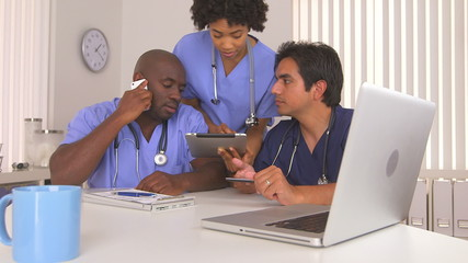 Multi ethnic group of doctors using computer and tablet