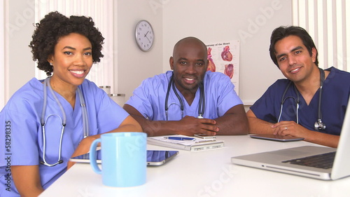 African American and Hispanic doctors using computer and tablet