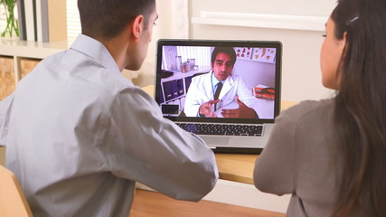 Hispanic couple video chatting with doctor