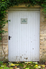 No entry sign on weathered panelled door