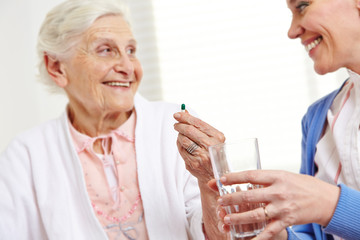 Seniorin nimmt Tablette im Krankenhaus
