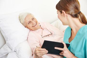 Krankenpflegerin liest Seniorin Buch vor
