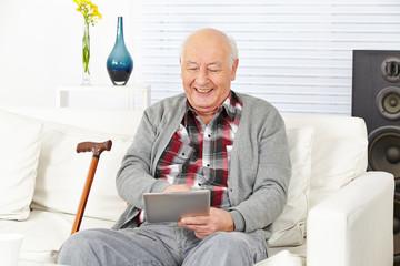 Senior mit Tablet PC zu Hause