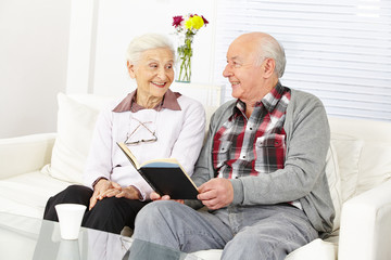 Senior liest seiner Frau aus Buch vor