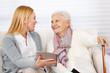 Frau zeigt Seniorin einen Tablet Computer