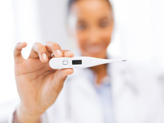 female doctor holding thermometer