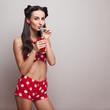 Drinking soda model in vintage shorts and bra