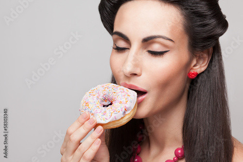 Close Up of eating donut beautiful woman.