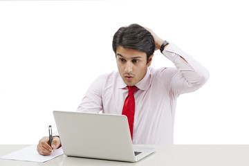 Businessman using a laptop and looking shocked