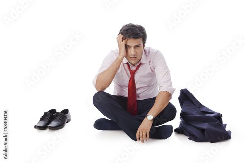 Businessman sitting on the floor and looking depressed