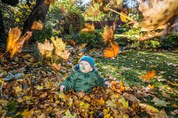 Kleinkind im herbstlichen Blätterregen