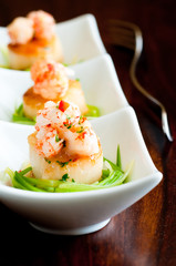scallops on a bed of leeks, topped with langostino lobster.
