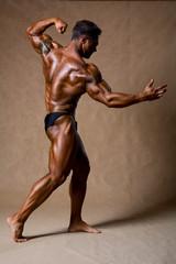 Bodybuilder flexing his muscles in studio.