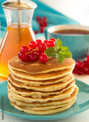 Homemade pancakes with honey and berries on a wooden table.