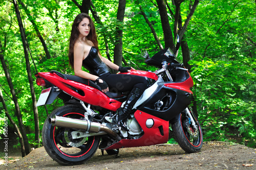 The girl on a sports bike in the woods
