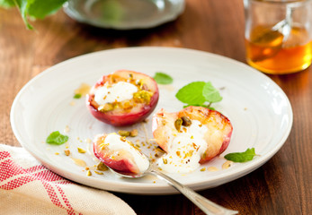 Closeup of grilled peaches with yogurt, honey and pistachios.