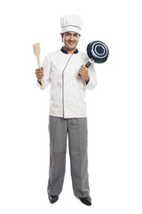 Portrait of a male chef holding a frying pan with spatula and smiling