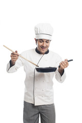Male chef preparing food in a frying pan