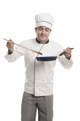 Male chef preparing food in a frying pan and  smelling