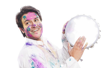 Man celebrating Holi with playing tambourine