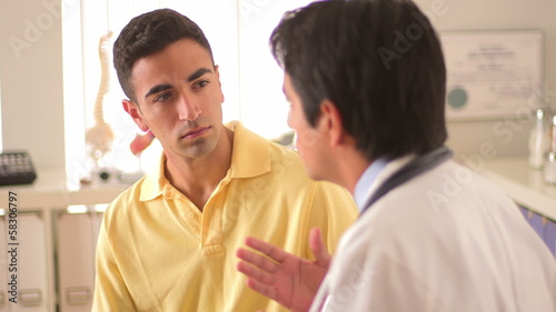 Mexican doctor talking to young male patient