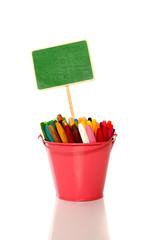 Green sign on metal bucket full of crayon.