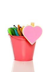 Heart shape sign on metal bucket full of crayon