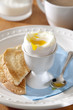 Closeup of a fresh soft-boiled egg at the breakfast table.