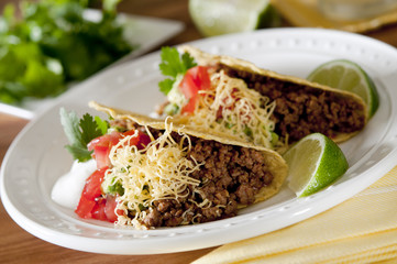 beef tacos with tomatoes, guacamole and sour cream.