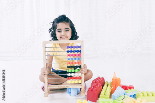 Portrait of a girl playing with abacus and smiling
