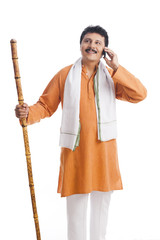 Man holding a wooden staff and talking on a mobile phone