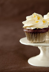 Closeup of a chocolate cupcake with vanilla frosting.