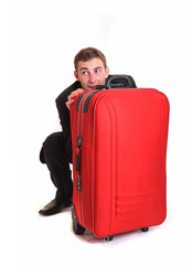 Fearful business man hide behind red luggage