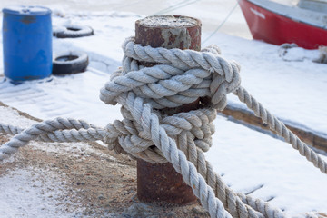 old bollard and frozen ship cable