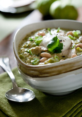 green chicken chili topped with sour cream and cilantro.