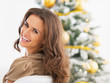 Portrait of smiling woman sitting in front of christmas tree