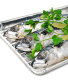 Fresh mackerel fish with parsley on the aluminium foil tray