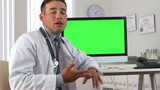 Hispanic doctor talking with green screen on computer in backgro