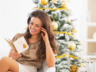 Smiling woman reading christmas postcard near christmas tree