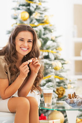 Happy young woman having latte macchiato near christmas tree