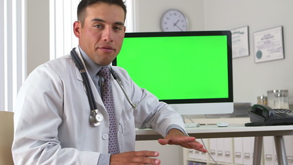 Hispanic doctor looking back to greenscreen on computer in backg