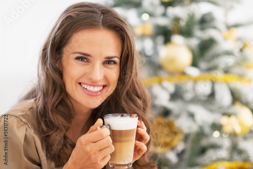 Happy woman with latte macchiato in front of christmas tree