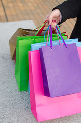 Parts of body of young woman with shopping bags