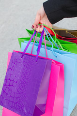 Arm of young woman with shopping bags