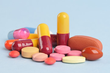 assortment of colorful pills and tablets isolated in blue