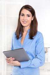 Freundlich lachende junge Frau im Büro in blauer Bluse